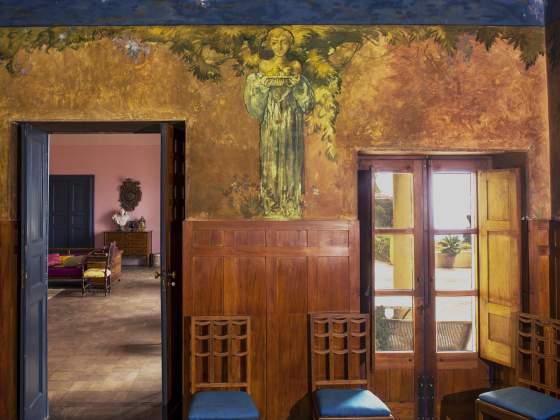 Una veduta della sala da pranzo di Casa Cuseni con l'elegante fregio pittorico
